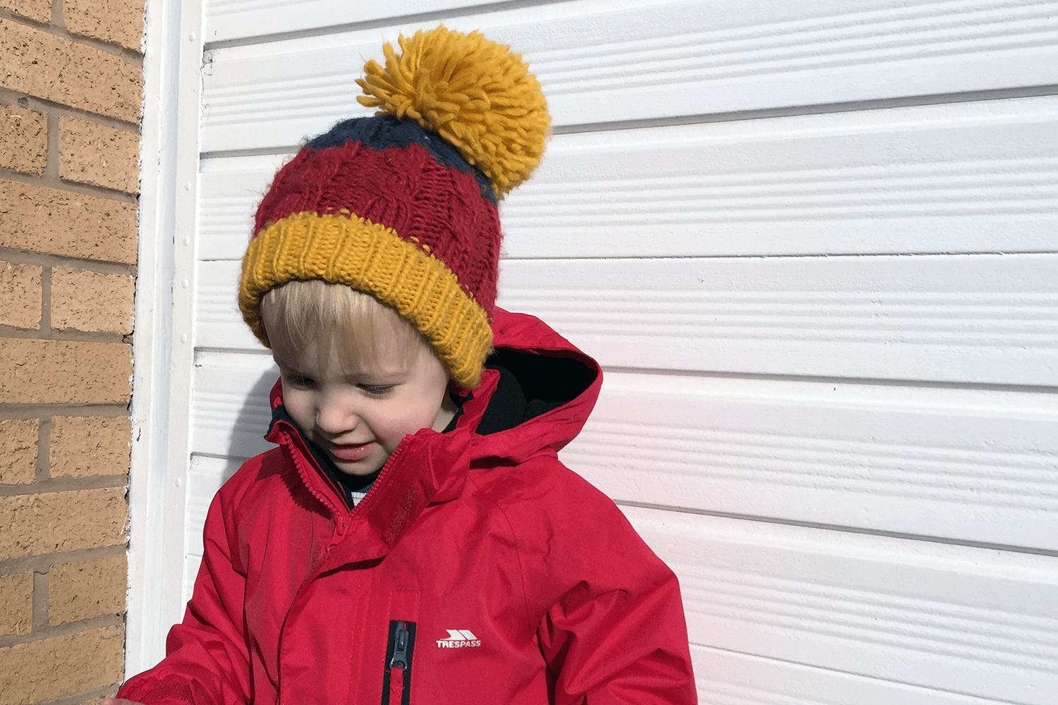 Gabe posing in front of the garage door in his hat with a massive bobble on top