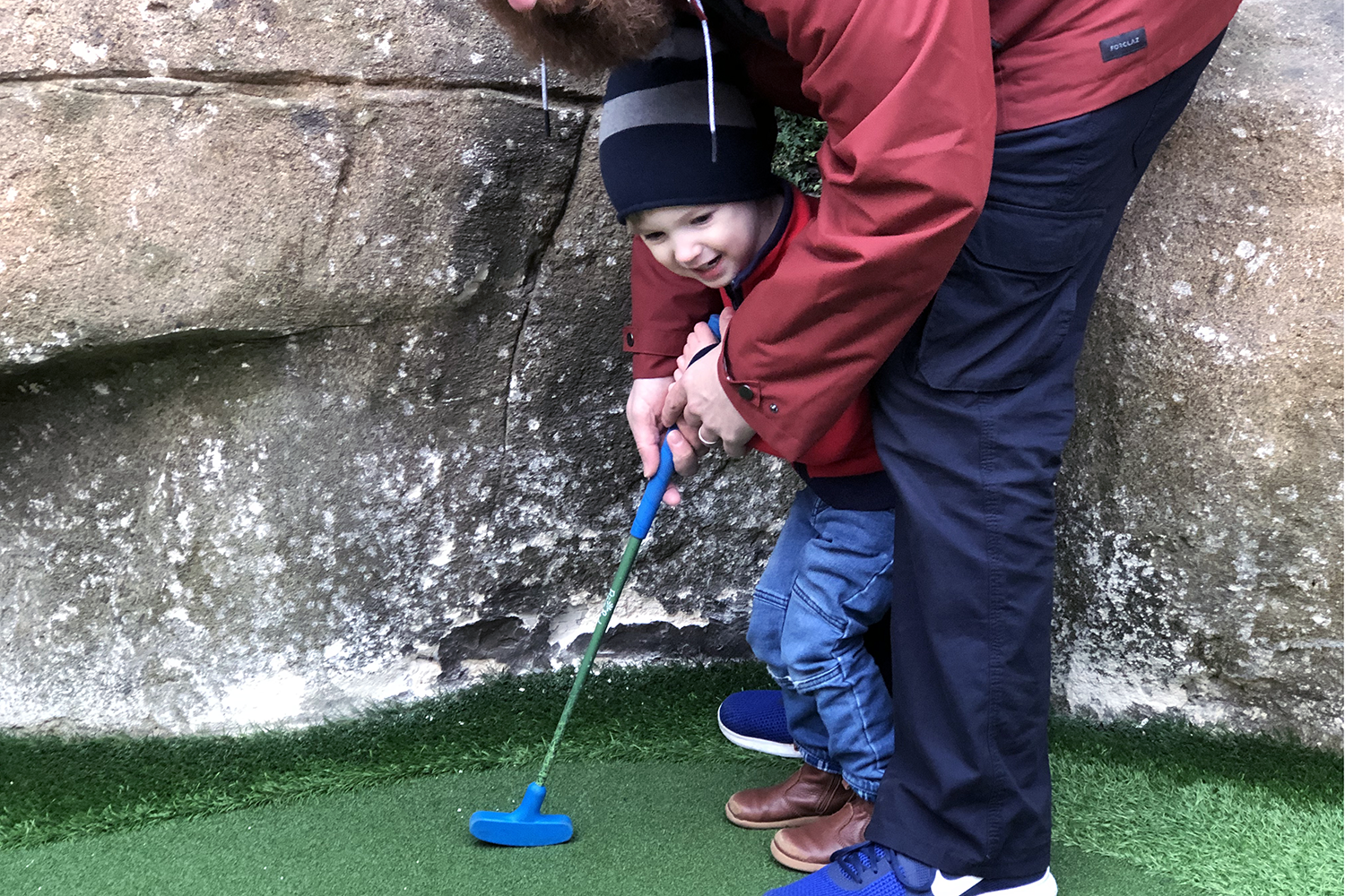 Gabe playing crazy golf with a little help from Daddy