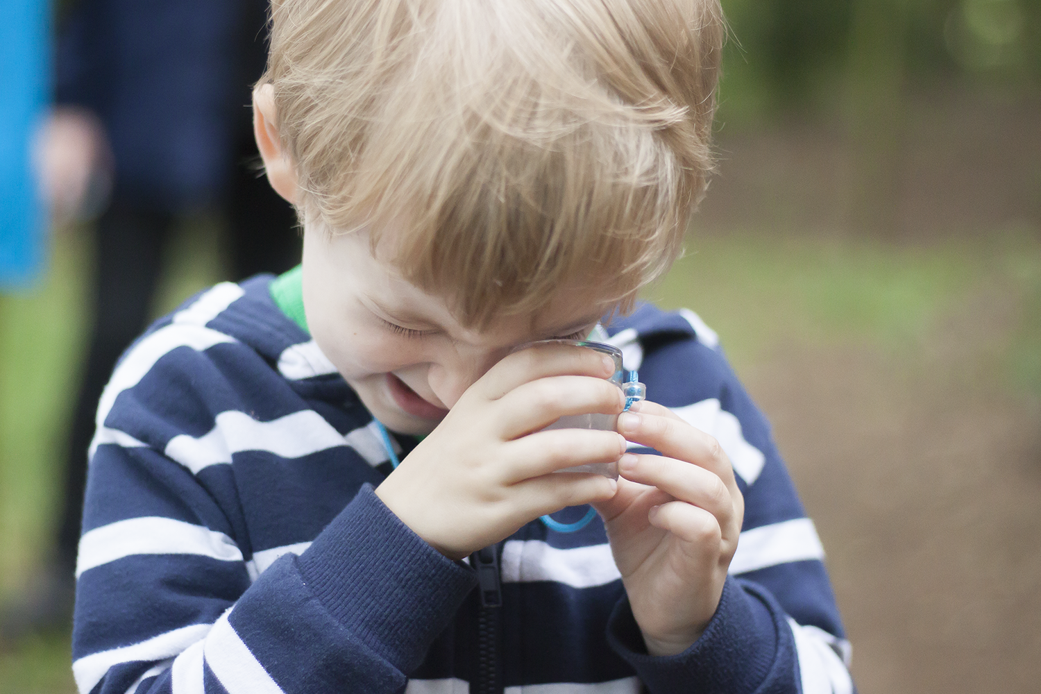 Gabe examining a bug he caught at his forest school party