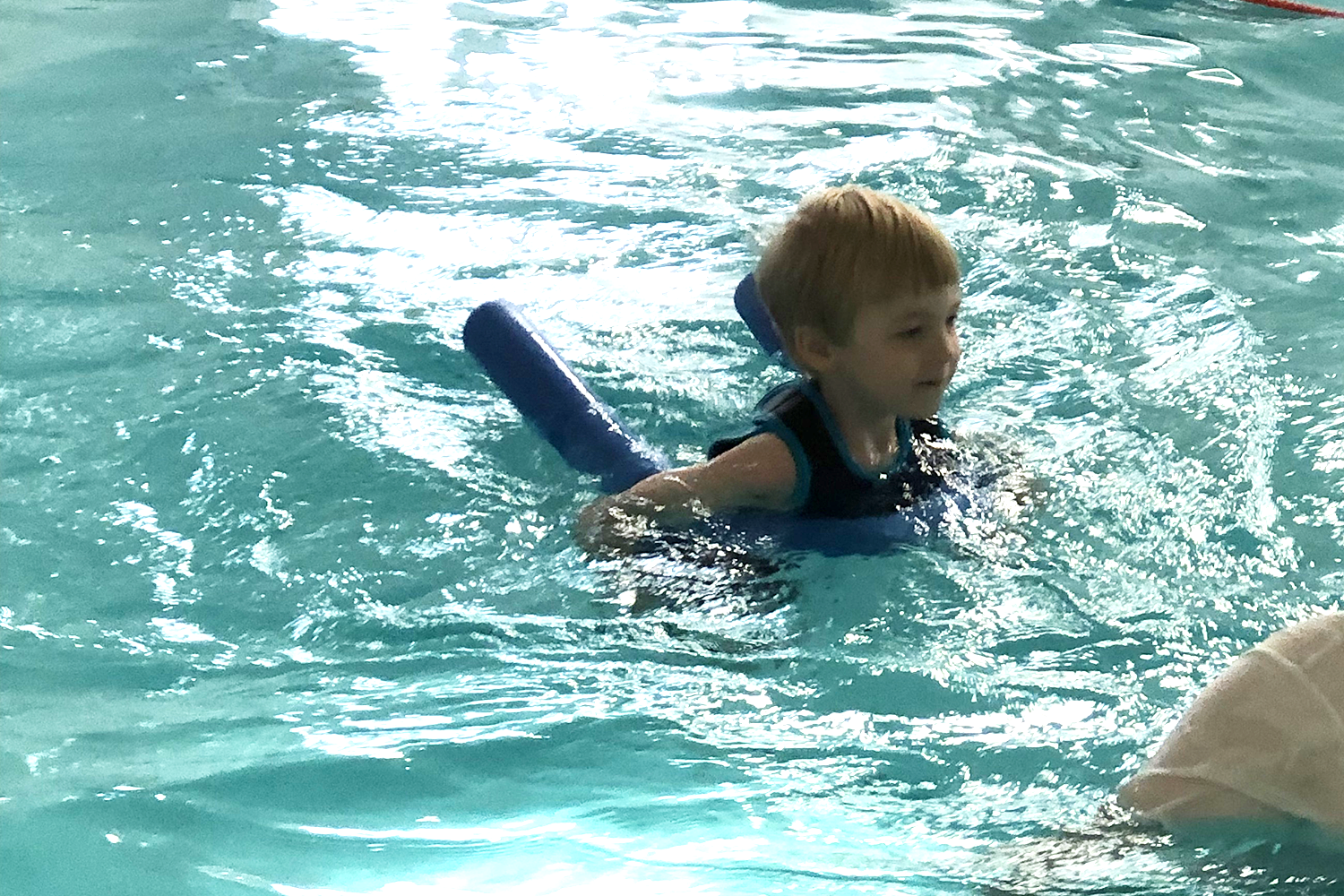 Gabe swimming with a pool noodle