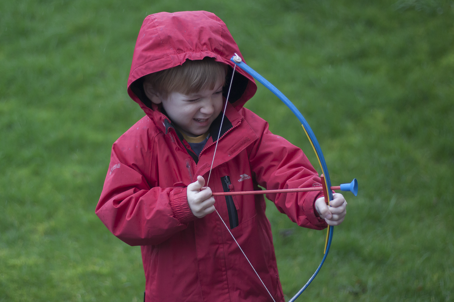 A boy in a red coat with a wooden bow and arrow