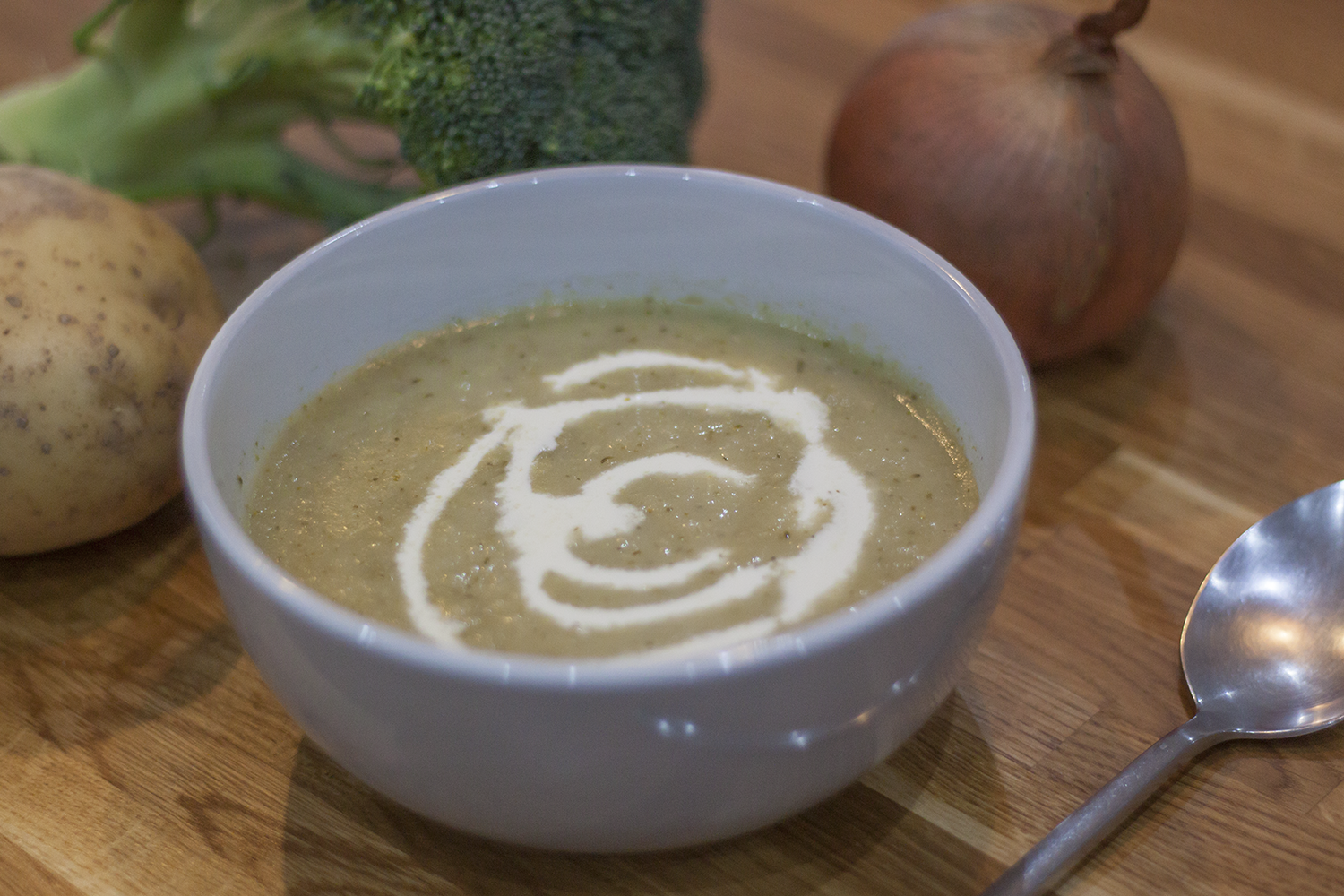 Bowl of broccoli soup with an onion, potato and broccoli behind