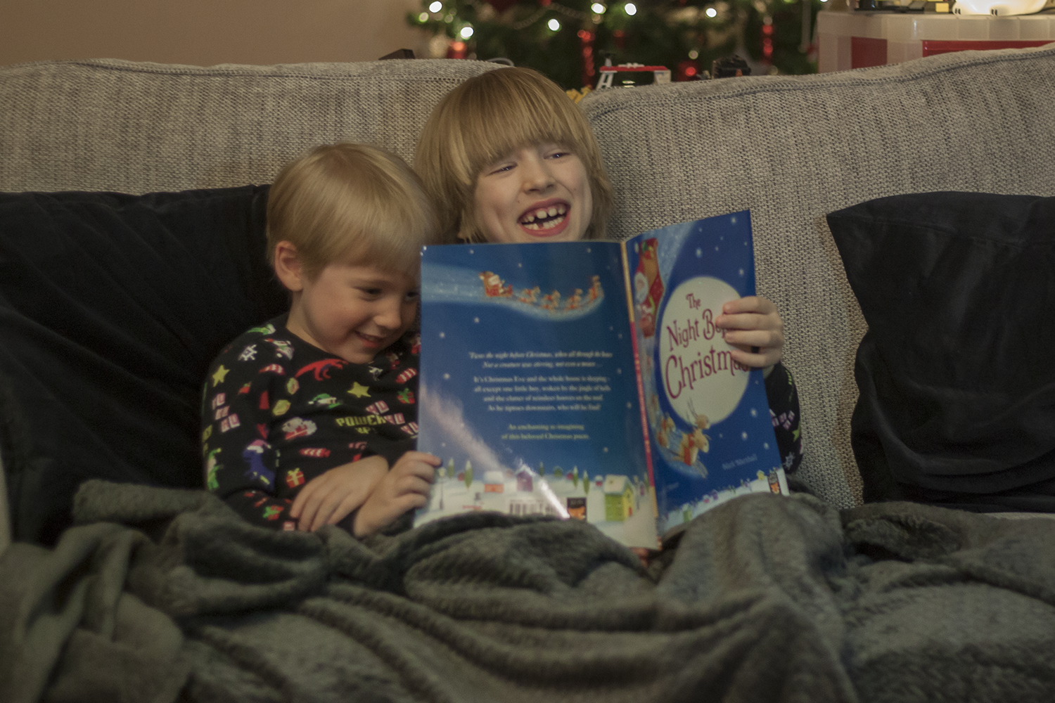 Two boys sitting on a sofa reading The Night Before Christmas