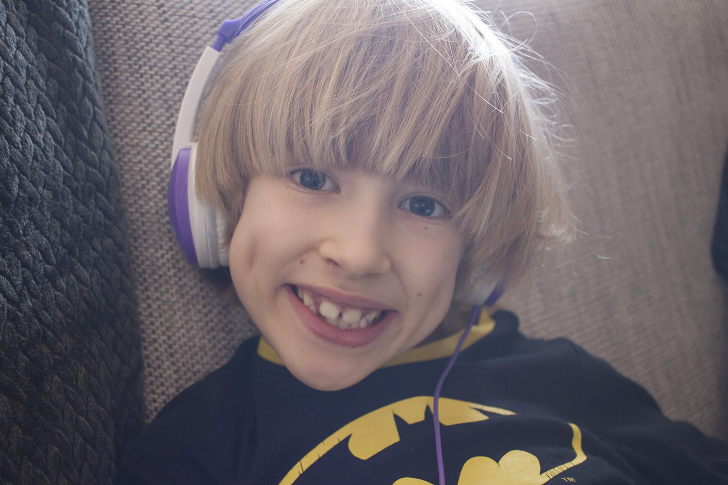 A boy with a batman t-shirt wearing purple and white headphones