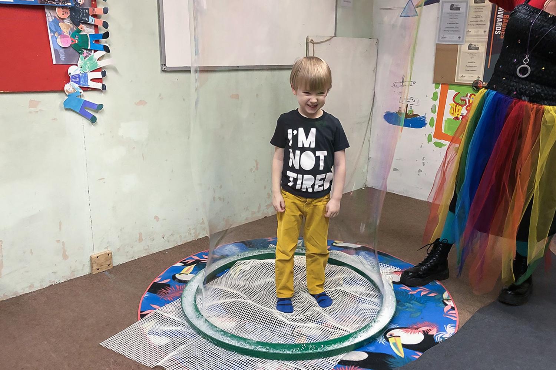 Boy standing inside a giant bubble