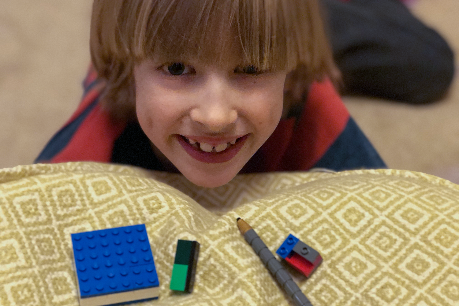 A boy grinning with some Lego on a cushion in front of him