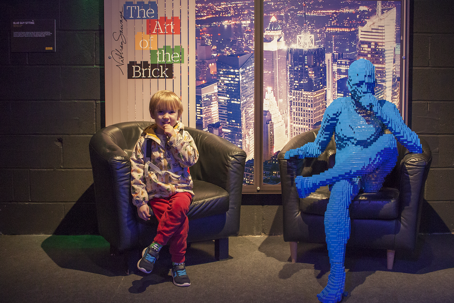 A boy copying the pose of a life size Lego man sitting in a chair