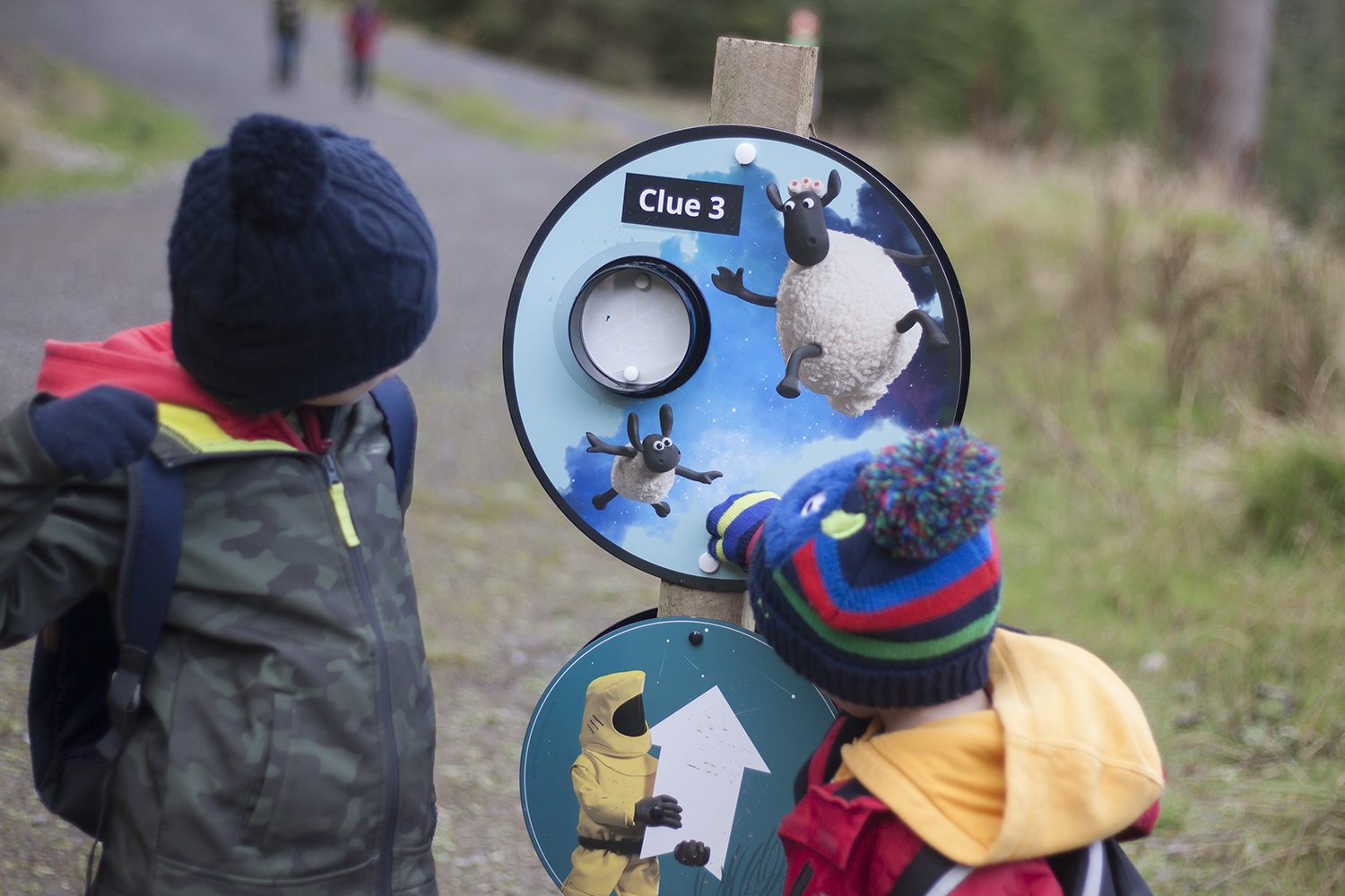 Two boys in knitted hats looking at a Farmageddon Glow Trail clue in Whinlatter Forest in the Lake District