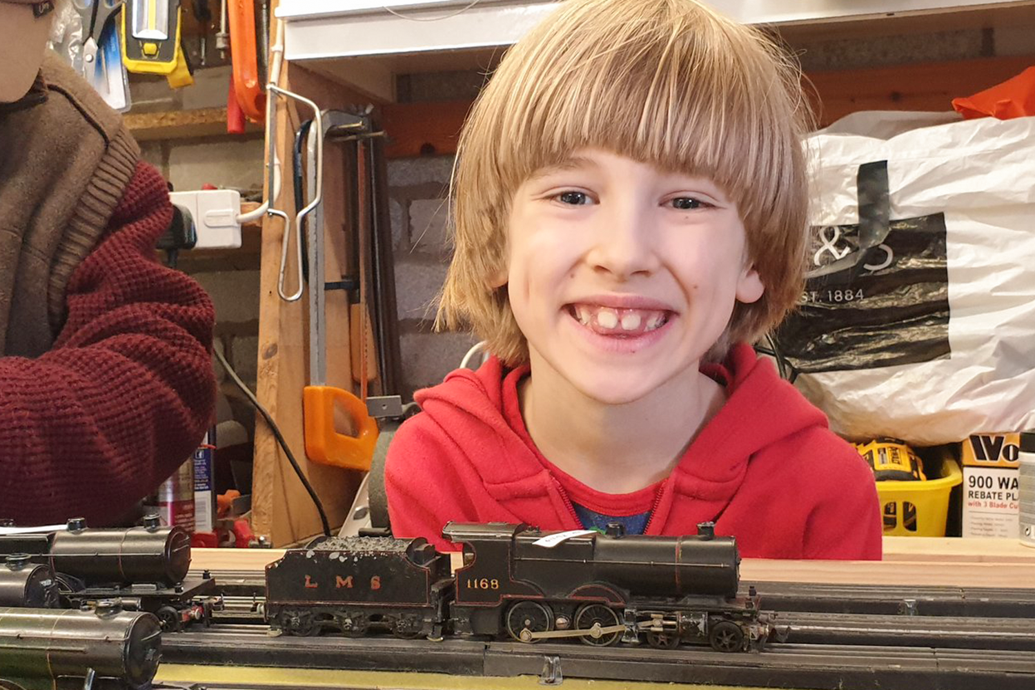 Toby smiling with a model train in front of him