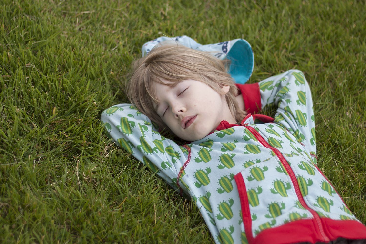 A boy lying on grass apparently sleeping. He's getting his vitamin D which can slow ageing