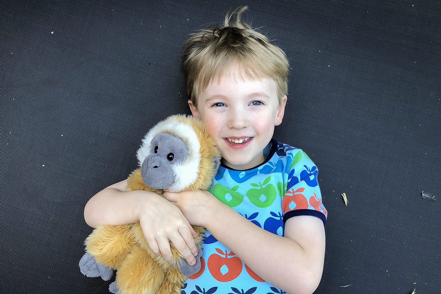 Gabe lying on the trampoline with his cuddly monkey