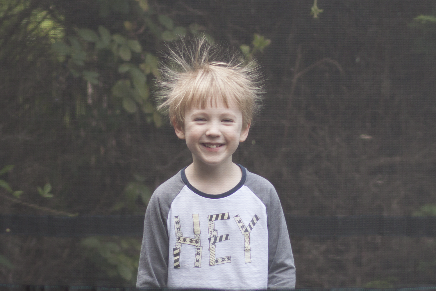 Gabe with his hair sticking up on the trampoline