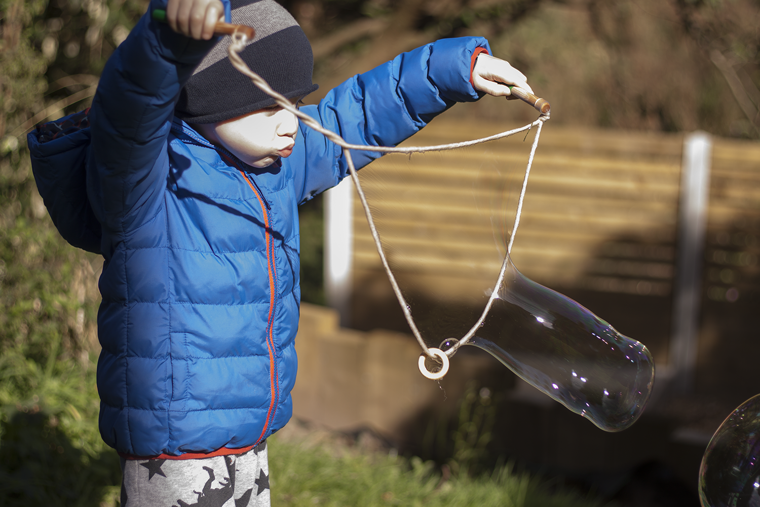 Gabe blowing bubbles in the garden