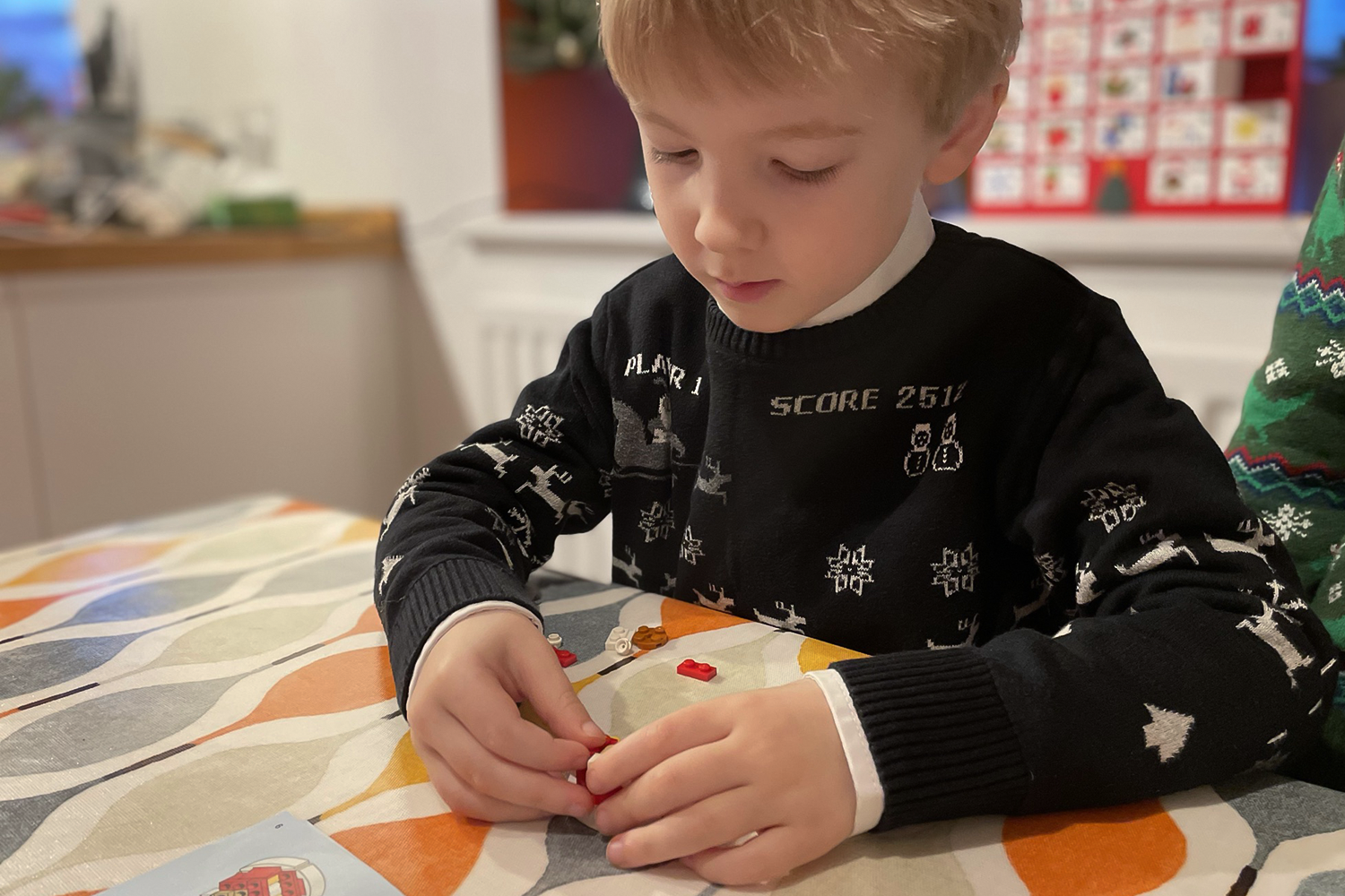 Gabe building Lego wearing a Christmas jumper