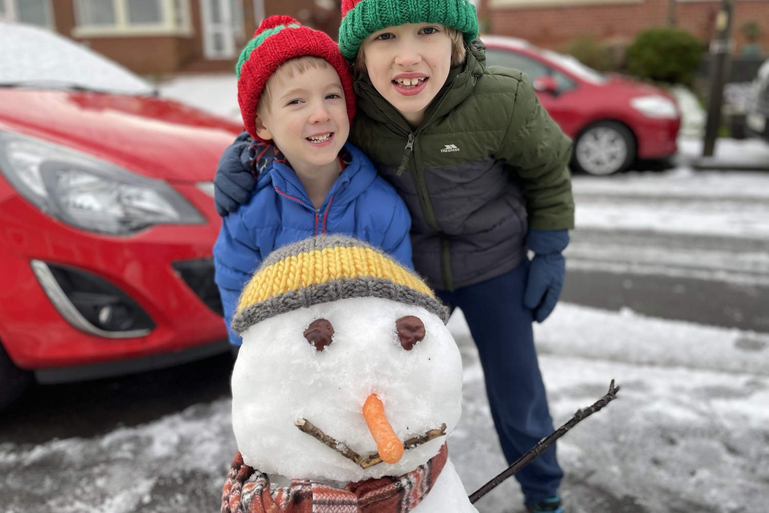 Toby and Gabe posing with their snowman