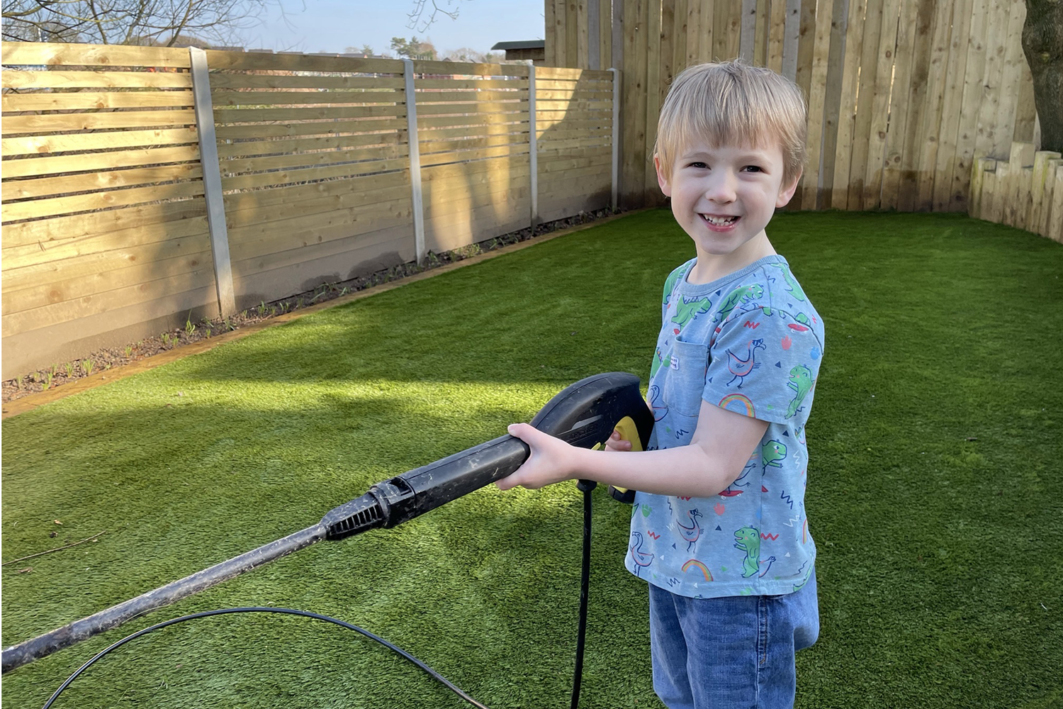 Gabe having a go with the pressure washer in the garden