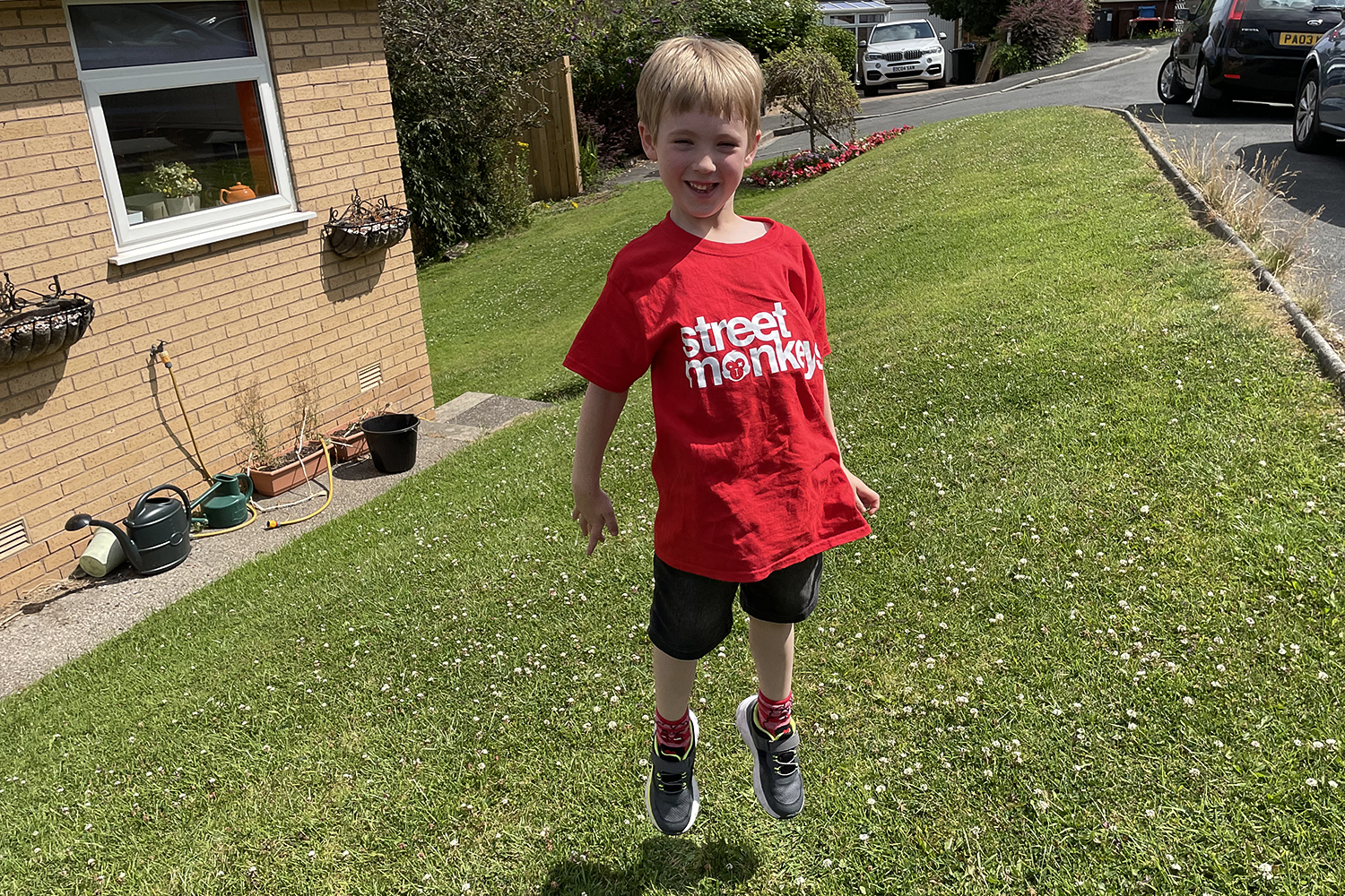 Gabe jumping on the grass outside our house wearing his red Street Monkeys t-shirt