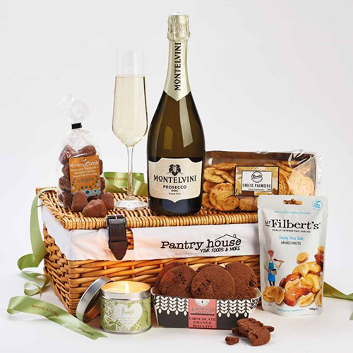 A wicker hamper with a champagne bottle on top and biscuits etc around it