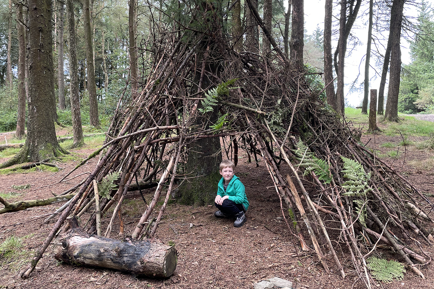 Gabe inside a big wooden shelter he made in the woods