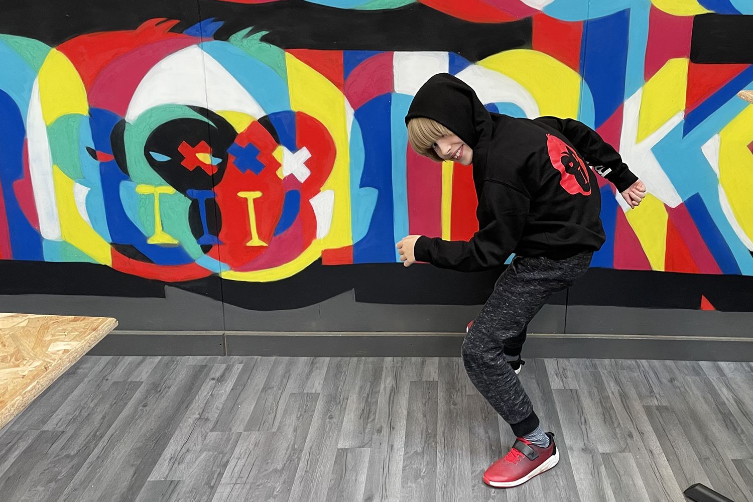 Toby doing a ninja pose in a black hoodie with the hood up in front of colourful monkey on the wall behind him